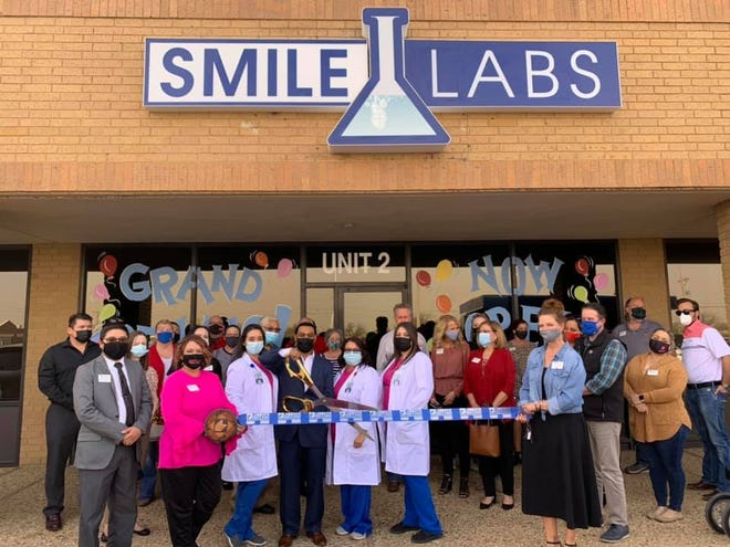 Ribbon cutting: SmileLabs Lubbock, 7412 University Ave. Holding scissors: owner Tyler Hernandez. Holding ribbon: Chamber Ambassadors Tracy Polk, left, and Stacy Williams. Also pictured: other staff, family, friends and Chamber Ambassadors. [Photo provided by the Lubbock Chamber of Commerce]