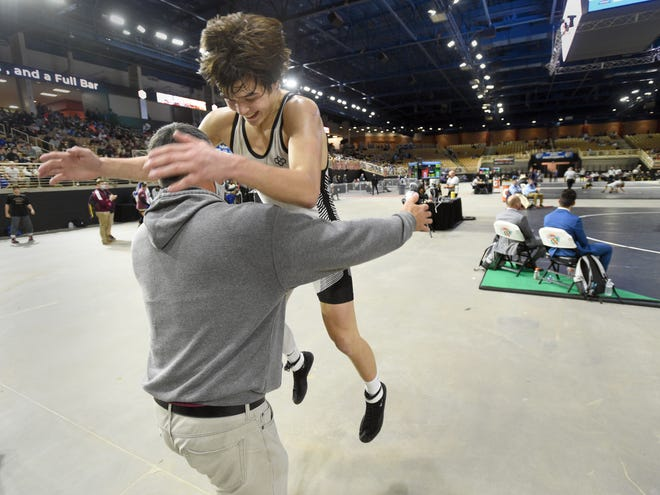 Lake Gibson's Brendon Abdon jumps into his dad's (Brian Abdon) arms after defeating Roman Garcia of Palmetto Ridge 5-0 at 152 pounds during the FHSAA Wrestling Finals in the Silver Spurs Arena in Kissimmee on Saturday.