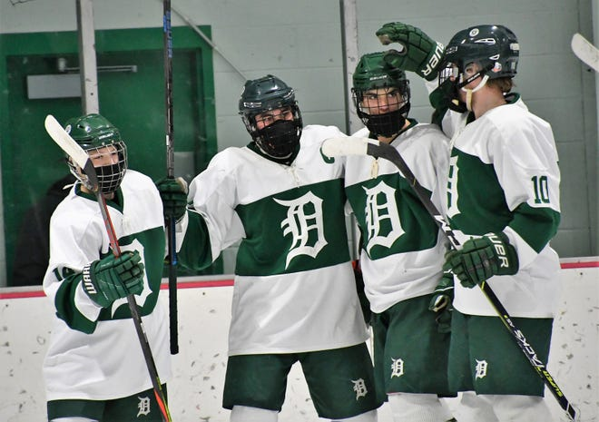 Dover celebrates Colby Roy's second goal during Saturday's 7-1 Division II playoff win over Winnacunnet at the Dover Ice Arena. Roy, second from the left, is with Parker Fleury, third from left, and Liam Lovering, right.