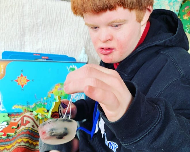 Cal Mahoney, a young man from Kennebunk, Maine, with Down syndrome, works on a science project in this undated photo. He and his family have been taking extensive precautions to keep him safe amid the COVID-19 pandemic.
