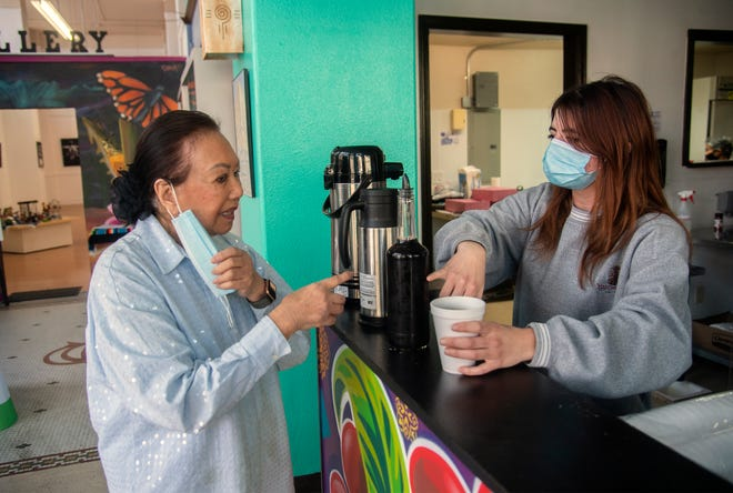 Elizabeth Blanchard, left, is served a cup of coffee by Jordan Boker at a coffee-tasting event at Terra Coffee in the Mexican Heritage Center in downtown Stockton in March. As COVID-19 rules change, businesseshave been put on the front lines of decidingwhat masking rules to put in place, and how to enforce them.