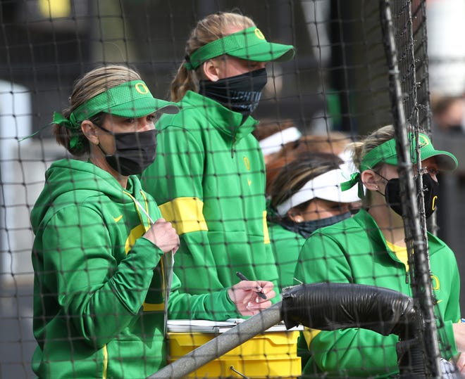 Oregon softball coach Melyssa Lombardi, left, watches the game against Boise State from the dugout at Jane Sanders in Eugene March 7, 2021.