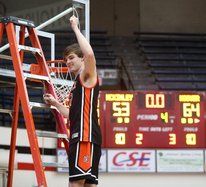 Brock Henne of Hoover cuts down the net following their 64-53 victory over McKinley in the DI district final at McKinley on Saturday, March 6, 2021.
