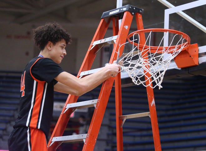 Hoover's Elijah Barker cuts down the nets at Memorial Field House after helping the Vikings beat McKinley 64-53 in Saturday's district championship game. March 6, 2021.