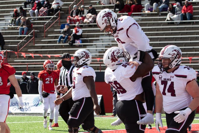 Rochester High School graduate Nic Baker, quarterback for Southern Illinois, is lifted into the air to celebrate his 17-yard touchdown run against Youngstown State on Saturday, March 6.
