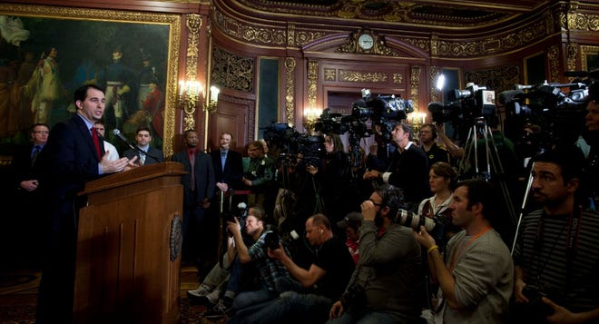 In this March 11, 2011, photo, Wisconsin Gov. Scott Walker speaks about the budget bill at a signing ceremony in Madison. The bill he signed bill stripped most collective bargaining rights from the state's public workers, except police and firefighters. The measure passed the state legislature following more than three weeks of protests that drew tens of thousands of people to the state Capitol in opposition.
