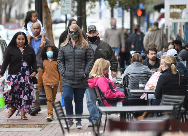 People walk down Front Street in downtown Wilmington, N.C., Saturday, March 6, 2021.