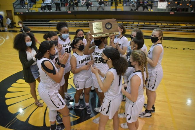 Topeka High's girls raised their Class 6A sub-state championship trophy after beating Washburn Rural 72-52 on Saturday at Topeka High.