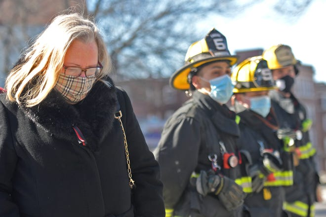 Worcester City Councilor At-Large, Kate Toomey, left, stands Sunday with Worcester firefighters, as they listen to William Breault of the Main South Alliance for Public Safety speak at the Main Street fire memorial, during the 31st anniversary of a tragic fire at 21 Florence St. in which four people perished. The memorial serves both as a reminder to the community of fire safety and of proactive fire solutions.