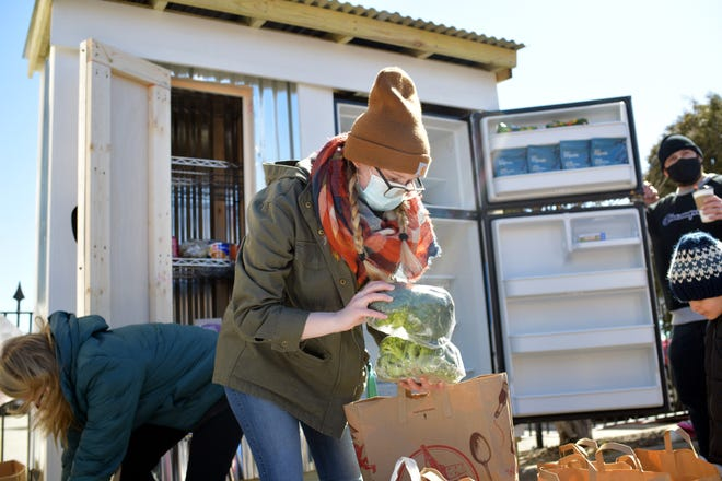A young woman unpacks healthy broccoli for the Worcester Community Fridge on Portland Street in March.