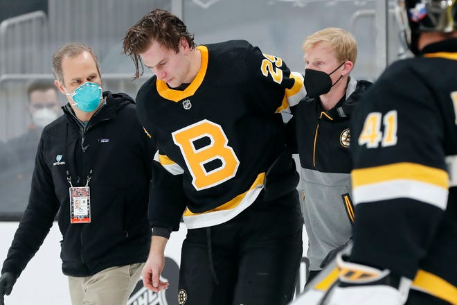 Boston Bruins defenseman Brandon Carlo is helped off the ice after an injury during a game against the Washington Capitals on Friday.