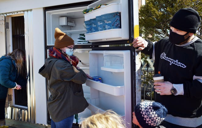 People begin stocking the fridge Sunday for the Worcester Community Fridges on Portland Street.