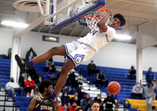 Gahanna Lincoln's Javan Simmons hangs on the rim after slamming down a dunk against Reynoldsburg in a Division I district final March 6.