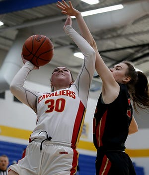 Guard Kara King (30) of Cincinnati Purcell Marian scores while being fouled by Worthington Christian's Katherine Weakley in Purcell Marian's victory in a Division III regional final girls basketball game on Saturday.