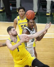 Michigan State Spartans forward Julius Marble II (34) rebounds against Michigan Wolverines center Hunter Dickinson (1) Sunday, March 7, 2021, at the Breslin Center in East Lansing.