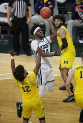 Michigan State Spartans forward Gabe Brown (44) scores against Michigan Wolverines guard Mike Smith (12) Sunday, March 7, 2021 at the Breslin Center in East Lansing.