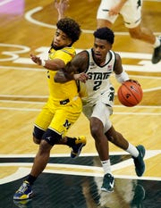 Michigan State guard Rocket Watts drives as Michigan guard Mike Smith defends during the second half Sunday, March 7, 2021, in East Lansing.