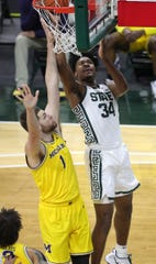 Michigan State Spartans forward Julius Marble II (34) drives against Michigan Wolverines center Hunter Dickinson (1) Sunday, March 7, 2021, at the Breslin Center in East Lansing.