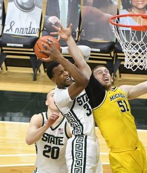 Marcus Bingham Jr dari Michigan State melakukan rebound di depan Austin Davis pada paruh pertama Minggu di East Lansing.