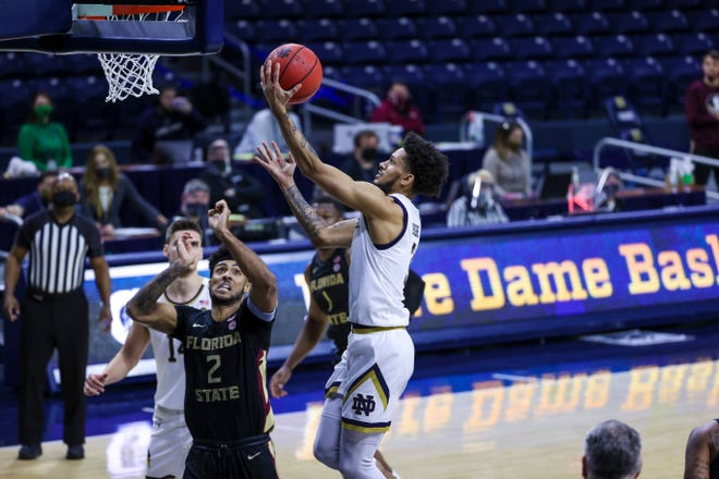Notre Dame junior guard Prentiss Hubb drives to the basket over Seminoles forward Anthony Polite at the Edmund P. Joyce Center in South Bend, IN., on March 6, 2021.