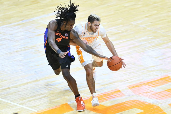 Tennessee's Santiago Vescovi (25) is guarded by Florida's Anthony Duruji, left, during last Sunday's game in Knoxville, Tenn. The Vols won 65-54 to earn the fourth seed in the SEC tourney.