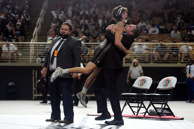 Jensen Beach High School's Jonny Dobbs celebrates with head wrestling coach Tom McMath on Saturday, March 6, 2021, after winning the Class 1A state title match against Florida High's Tyler Reeve at the FHSAA State Wrestling Championships in Kissimmee.