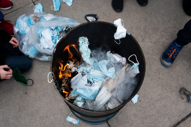 Attendees threw surgical masks into a fire during a burning masks event at Idaho State House on March 6, 2021 in Boise, Idaho.