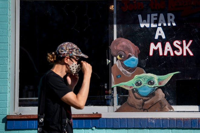 A woman passes a sign advising people to wear their masks outside Amy's Ice Creams on Tuesday, March 2, 2021 in Austin, Texas. Texas Gov. Greg Abbott rescinded the state wide mask mandate Tuesday afternoon with plans for businesses to open at 100 percent capacity next week.