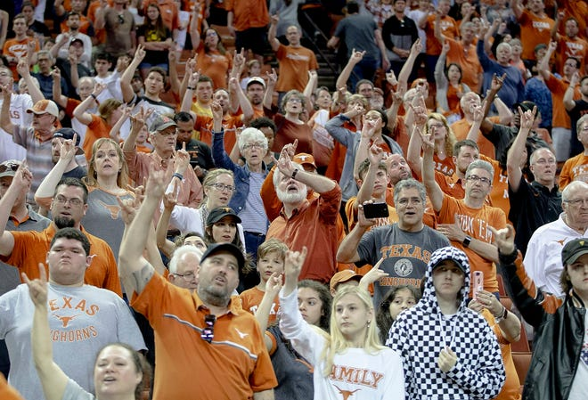 """Texas fans hold up their """"Hook 'Em Horns"""" signs during the playing of """"The Eyes of Texas"""" following Texas' 78-76 win over Xavier in a second round NCAA National Invitation Tournament college basketball game on Sunday, March 24, 2019, in Austin, Texas."""