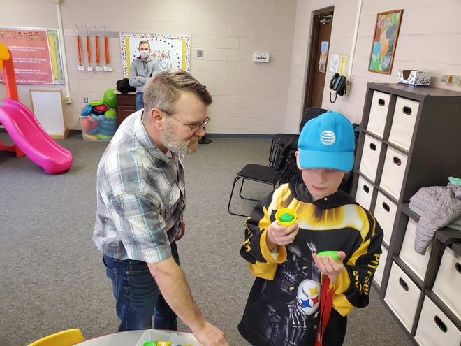 Volunteer Dean Downing works with Zavier Coffman during Ashland Special Needs Respite Care at Grace Church.