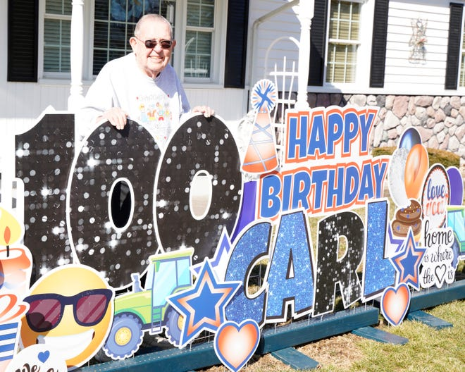 Longtime Adrian resident Carl Lamphier celebrated his 100th birthday last week and was surprised when his neighbors threw him a socially-distant party complete with a yard card display. Lamphier poses for a photo in front of his birthday card display.
