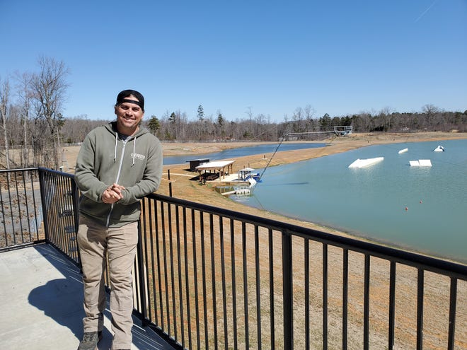 Morgan Batchelor, co-owner of Elevated Wake Park, stands on the second-story deck overlooking the wake park he opened with his dad in June 2020. The park will grow this year with an addition of an aqua park in the smaller lake visible over Batchelor's shoulder, a restaurant and summer camps.