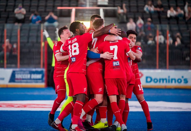 Kansas City Comets players mob teammate Lucas Sousa (7) after he scored the go-ahead goal with just 1:41 left. Sousa's goal completed a hat trick for him and a 7-6 win for the Comets.