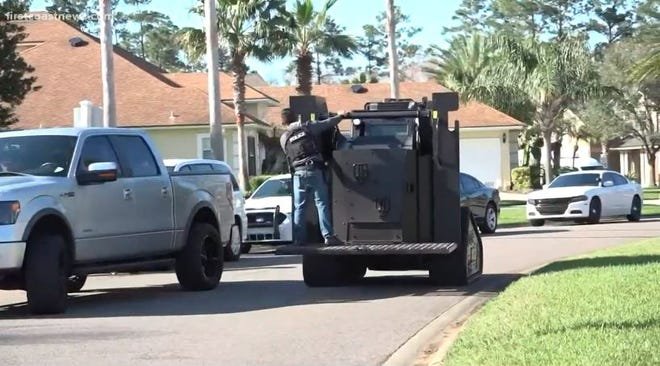 A Clay County Sheriff's Office SWAT vehicle rolls down a Fleming Island street on Sunday as negotiators tried to get a man inside a home to surrender.