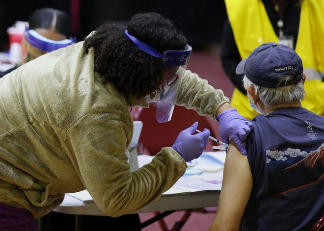 A health care worker vaccinates a man at a community COVID-19 vaccination clinic run by the Philadelphia Department of Public Health at University of the Sciences' Bobby Morgan Arena in West Philadelphia on Feb. 27, 2021.