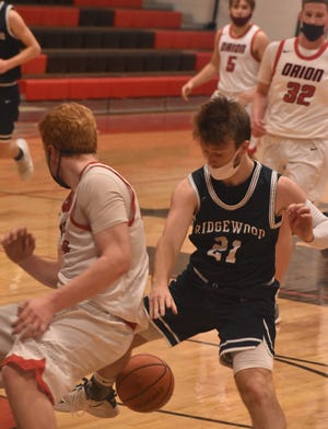Chasing down a loose ball on Thursday, March 4, are Orion's Josh Spranger, left, and Ridgewood's Mitchell Brooks. They were competitors in the varsity game in the Charger gym.