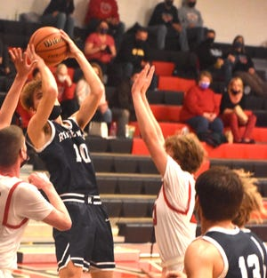 Ridgewood's Ganon Greenman, center, gets off a shot during the varsity game with Orion on Thursday, March 4, in the Charger gym. Greenman is the career scoring record-holder for the Ridgewood program and AlWood High School.