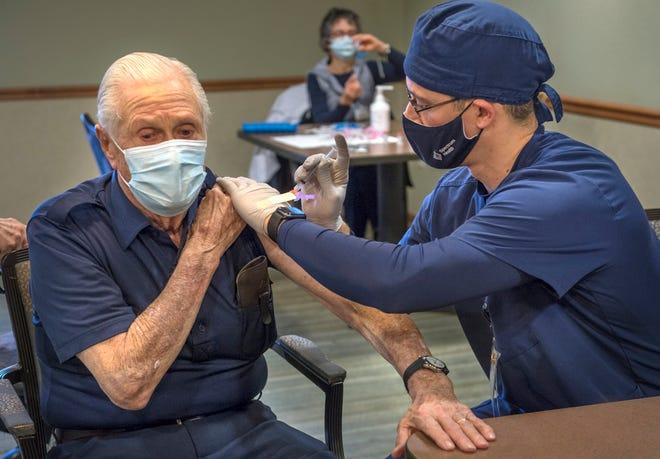 A Spectrum Health administers the COVID-19 vaccine to Don Cecconi.