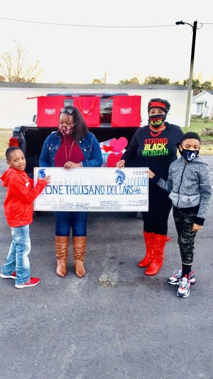 A group of community helpers recently raised and donated money and merchandise to Josh Boone to aid in his recovery. Boone was injured in a vehicle accident in October 2020 in Kinston. Pictured, Josh Boone, his mother Shekiah Wilder, Felecia Ward Brinkley and Alexander Brinkley. [CONTRIBUTED PHOTO]