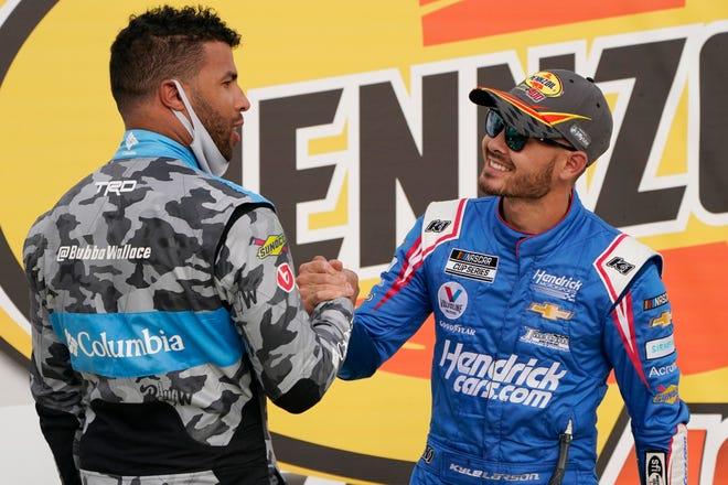 Bubba Wallace, left, congratulates Kyle Larson after Larson won a NASCAR Cup Series auto race Sunday, March 7, 2021, in Las Vegas.