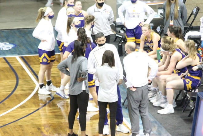 Western Illinois coach JD Gravina talks with his staff while his team huddles during the Summit League Tournament quarterfinal game against Kansas City.