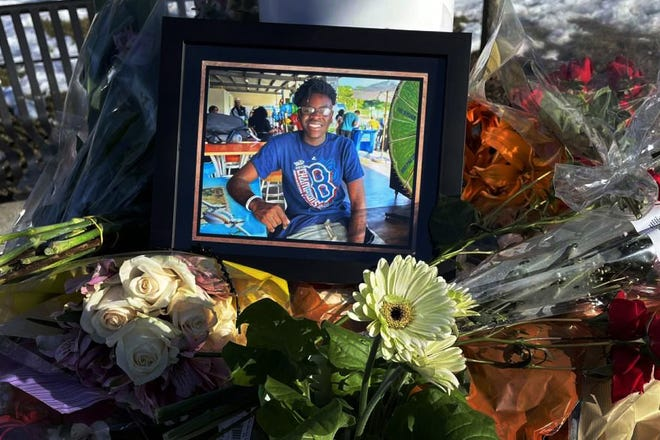 A memorial at the flag pole outside Natick High School pays tribute to Natick High junior Giovanni Taboh, who died following an accident on Saturday night in Canton.