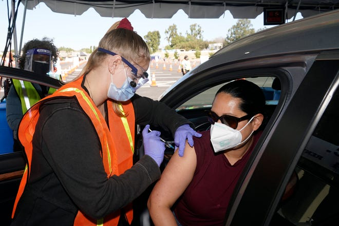 In this March 2, 2021, file photo, Vanessa Guerra, at right, a special education teacher at Grant Elementary School in Hollywood, receives a shot of the Moderna COVID-19 vaccine from nurse Kelly Mendoza at a site for employees of the Los Angeles school district in the parking lot of SOFI Stadium in Inglewood, Calif. Cities and states are rapidly expanding access to vaccines as the nation races to head off a resurgence in coronavirus infections and reopen schools and businesses battered by the pandemic.