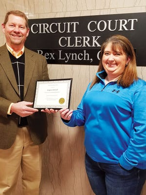 Anderson County Circuit Court Clerk Rex Lynch presents his bookkeeper Angela Metcalf with a certificate of appreciation after finding out there were no audit findings in his offices for the second year in a row.