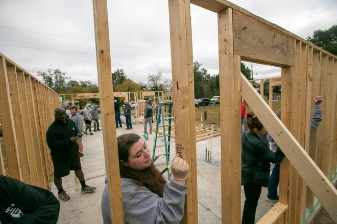 Volunteers and staff write wishes on the studs after they they raised the walls on two Habitat for Humanity Houses on West Fort King St, on Thursday December 17, 2020 in Ocala, Florida.