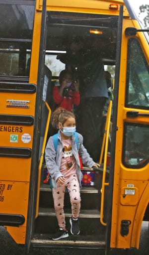 A handful of students arrive on the bus to the first day of in-person classroom lessons in Weymouth Tuesday, Oct. 13, 2020.