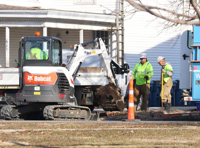 Workers for Illinois American Water Company dig a ditch as they prepare to do some utility work on West Madison Street Monday.
