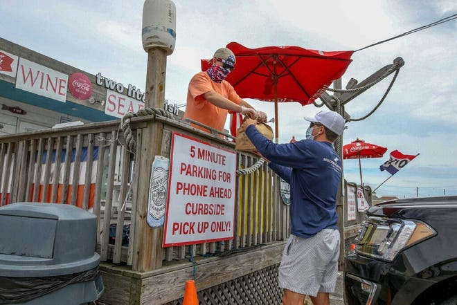 Kevin Crimmins hands off an order to a waiting customer at Two Little Fish, a clam shack at Misquamicut Beach in Westerly, in mid-July of last year. Officials in Westerly are considering making permanent an regulation allowing allowing restaurants and bars to serve beer along the beach in Misquamicut.