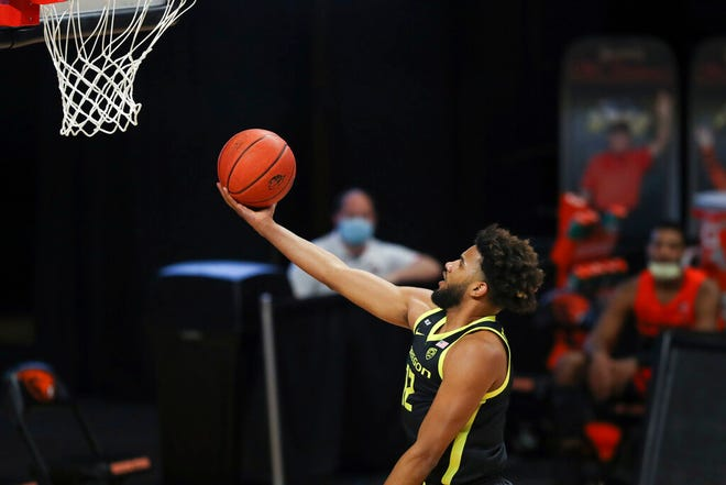 Oregon's L.J. Figueroa (12) drives to the basket during the first half against Oregon State Sunday. (AP Photo/Amanda Loman)