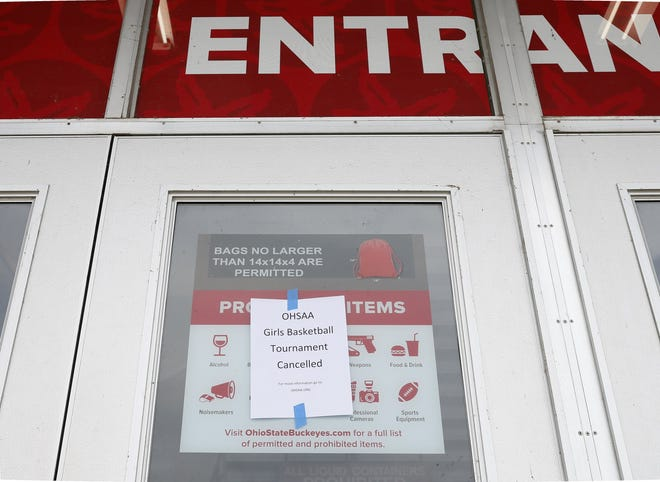 Signs were posted on the doors of St. John Arena after the OHSAA announced that all winter sports tournament postseason play was suspended on Thursday, March 12, 2020. [Barbara J. Perenic/Dispatch]